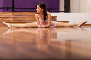 22764091 - beautiful ballet dancer stretching and doing a leg split in a dance studio lots of copy space on the bottom